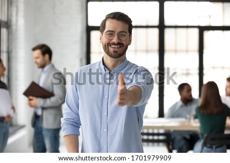 Smiling young Caucasian businessman stretch hand welcome new employee or worker at workplace, happy European male boss or CEO greeting meeting newcomer in office, employment concept