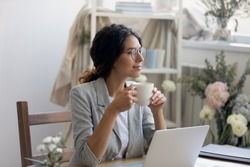 Smiling young Caucasian businesswoman in glasses drink coffee enjoy morning in home office. Happy female fashion designer stylist look in distance dreaming thinking, work in cozy creative workplace.