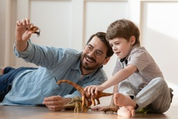Smiling young Caucasian father and little preschooler son sit on warm floor at home play with rubber dinosaur figures together, playful dad and small boy child have fun engaged in game at home