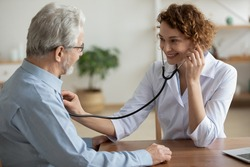 Smiling young Caucasian female doctor hold stethoscope listen to elderly male patient heart rate. Happy caring woman nurse use phonendoscope measure heartbeat of mature man in hospital.