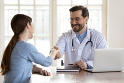 Smiling young Caucasian male doctor shake hand greeting get acquainted with female patient in hospital, happy man physician handshake woman client make agreement sign health insurance in clinic