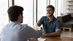 Smiling young Caucasian male employee handshake greet employer or recruiter at office interview or work talk. Happy businessmen or business partners shake hands closing deal making agreement.