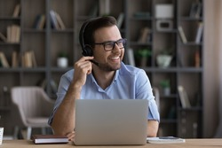 Smiling young Caucasian male employee in headphones work distant on laptop at home office thinking dreaming. Happy millennial man in earphones busy using computer talk on video call with client.