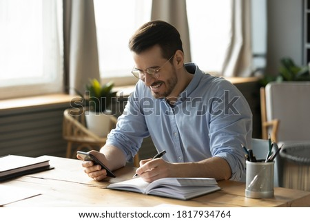 Smiling young Caucasian man sit at desk at home office workplace look at cellphone screen watch webinar making notes. Happy millennial male use smartphone summarize plan writing in journal.