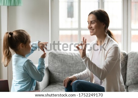 Smiling young Caucasian mom and little daughter make hand gesture learn speak sign language at home, happy mother or nanny practice nonverbal talk with small disabled girl child, disability concept