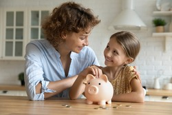 Smiling young Caucasian mom and little daughter put coins money into piggybank mange family budget together. Happy mother and small girl child saving for future feel economical provident.