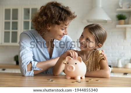 Smiling young Caucasian mom and little daughter put coins money into piggybank mange family budget together. Happy mother and small girl child saving for future feel economical provident. Stock fotó ©