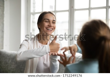 Smiling young Caucasian mom or nanny make hand gesture practice nonverbal talk with little girl child, positive female teacher or tutor learn sign language with small disabled kid, disability concept