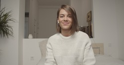 Smiling young caucasian woman blogger vlogger influencer sit at home speaking looking at camera talking make video chat, conference call record lifestyle blog vlog, webcam view