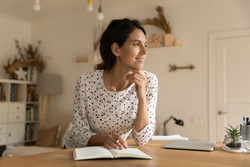 Smiling young Caucasian woman sit at table at home write make list in notebook look in distance dreaming thinking. Happy millennial female handwrite in notepad visualize or imagine. Planning concept.