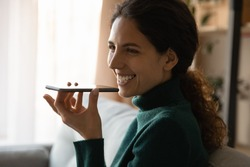Smiling young Caucasian woman use cellphone gadget activate digital voice assistant app on device. Happy millennial female talk on loudspeaker on smartphone or record audio message on cell.