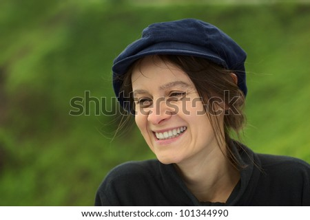 Smiling young Caucasian woman with a blue gatsby cap in a park (Selective Focus, Focus on the left eye)