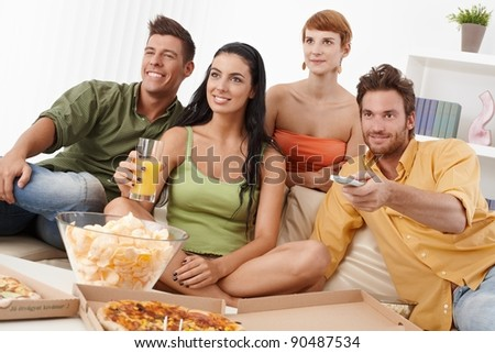 Smiling young companionship watching tv together, having pizza and chips.?