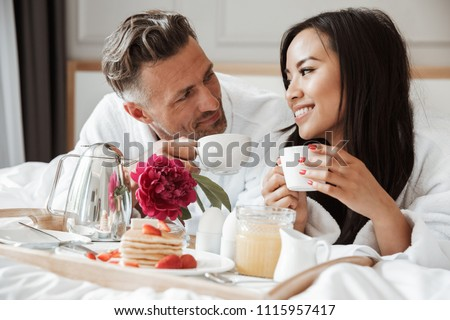 Smiling young couple dressed in bathrobes having romantic breakfast while lying on bed and drinking coffee