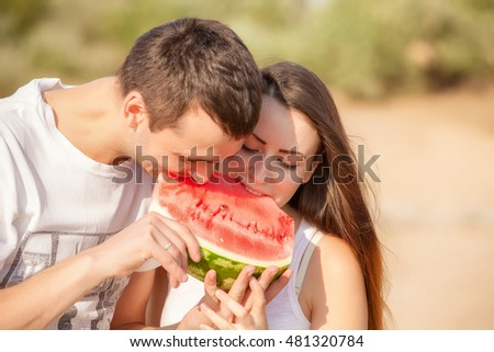 smiling young couple eating fresh melon together #481320784
