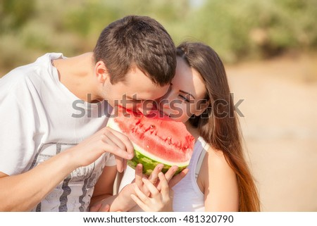 smiling young couple eating fresh melon together #481320790
