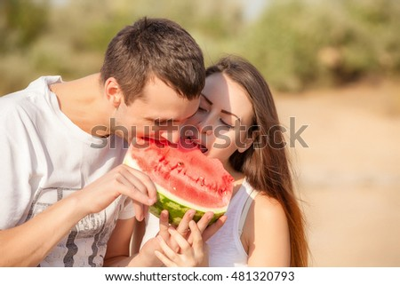 smiling young couple eating fresh melon together #481320793