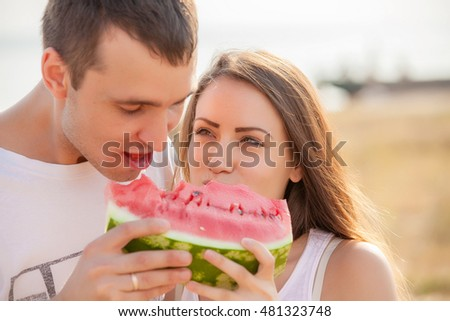 smiling young couple eating fresh melon together #481323748