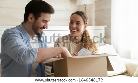 Smiling young couple feel overjoyed unpack cardboard package ordering buying goods over internet use delivery service, happy millennial husband and wife customers open box purchase shopping online
