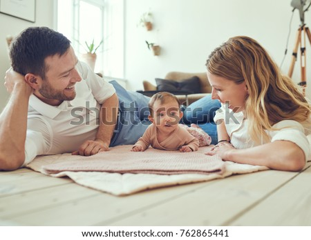 Smiling young couple lying together on blankets on their living room floor at home with their adorable baby daughter
