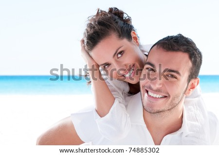 Smiling young couple piggyback at beautiful summer beach stock photo