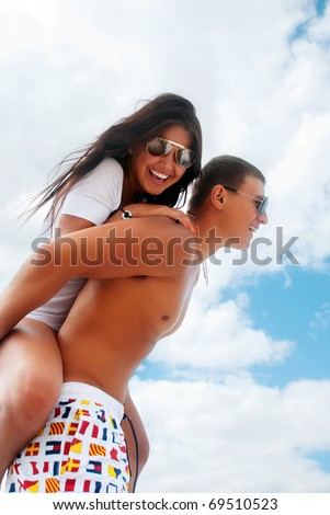 Smiling young couple piggybacking at beach