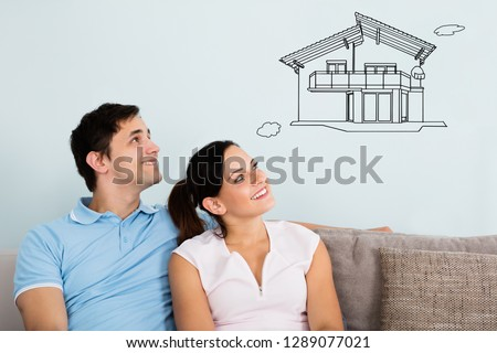 Smiling Young Couple Sitting On Sofa Thinking Of Getting Their New House #1289077021