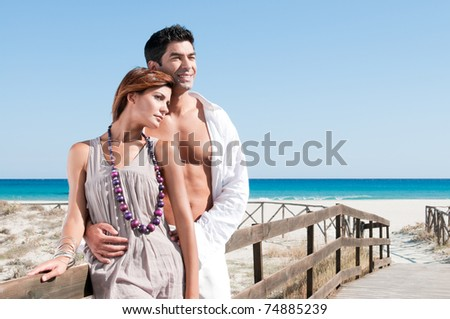 Smiling young couple staying together at summer beach