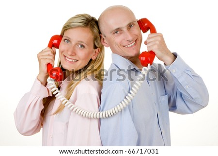 Smiling young couple stood back to back connected with red telephones, isolated on white background.