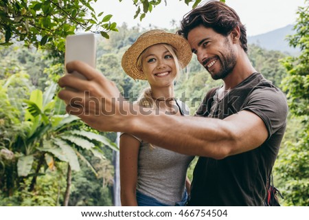 Smiling young couple taking selfie with waterfall in background. Man and woman in forest taking self portrait with their cellphone.