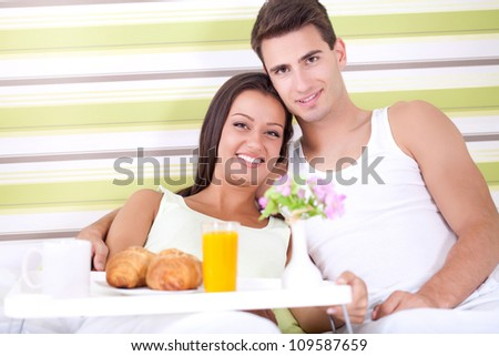 Smiling young couple together getting ready to enjoy breakfast in bed