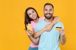 Smiling young couple two friends guy girl in blue pink t-shirts isolated on yellow background studio. People lifestyle concept. Mock up copy space. Using mobile phone, hold credit bank card, hugging.