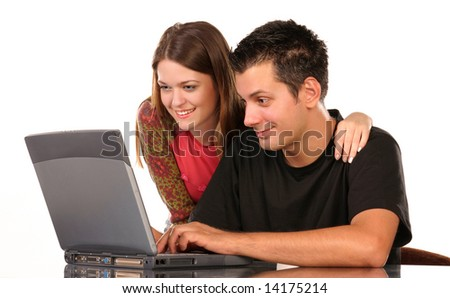Smiling young couple, using a laptop, on white background