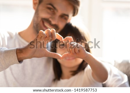 Smiling young dad and little daughter hug showing love sign express family bonding and care, happy parent embrace preschooler girl kid make hand heart gesture, enjoy tender moment together