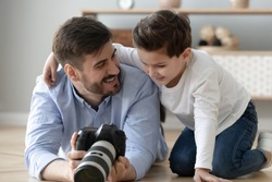 Smiling young dad lying on floor with preschooler son holding professional camera show pictures to child, happy father photographer and boy kid making pictures together with photographic device
