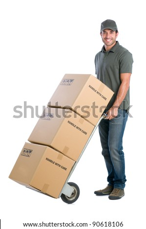 Smiling young delivery man moving boxes with dolly, isolated on white background
