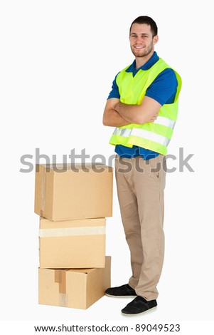 Smiling young delivery man with arms folded against a white background