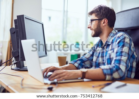 Smiling young developer typing code on laptop and looking at screen in office