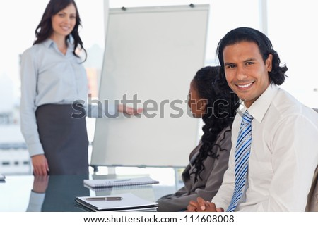 Smiling young employee listening to the presentation given by an executive - stock photo