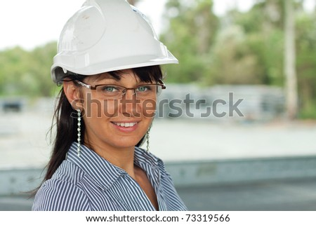smiling young engineer woman wears glasses and helmet in the warehouse