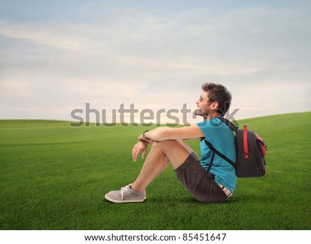 Smiling young explorer sitting on a green meadow