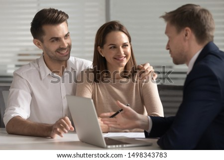 Smiling young family couple consulting with lawyer, bank worker, financial advisor or real estate agent. Happy husband and wife taking loan, mortgage, purchasing first apartment, medical insurance.
