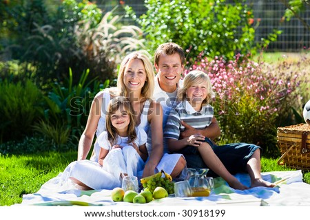 Smiling young family having picnic in a park
