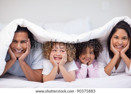 Smiling young family hiding under the blanket