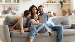 Smiling young family with little preschooler kids sit on couch in kitchen make self-portrait picture on cell together, happy parents with small children have fun take selfie on smartphone at home