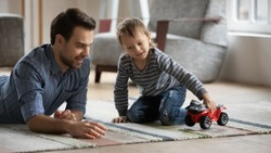 Smiling young father lying on floor carpet playing favorite toy car with little cute child boy. Happy daddy enjoying free weekend or evening playtime with kid son, family hobby pastime concept.