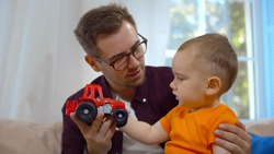 Smiling young father playing favorite toy car with little boy. Portrait of happy man in glasses babysitting cute baby son playing together with red car on couch in living room