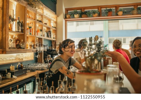 Smiling young female bartender standing behind the counter of a trendy bar taking drink orders from customers #1122550955