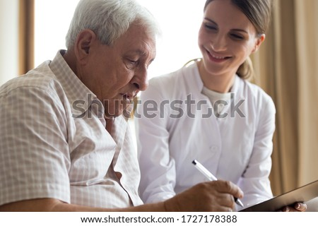 Smiling young female doctor or caregiver visit senior male client close deal at home, positive woman medical worker consult mature man sign insurance contract, offer help, elderly healthcare concept