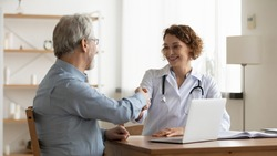 Smiling young female doctor shake hand close health insurance deal with elderly patient at consultation in hospital. Happy woman GP handshake greeting get acquainted with mature man in clinic.